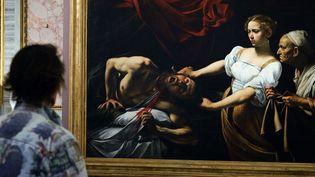"""Un visiteur devant¨""""Judith décapitant Holopherne"""" du Caravage, à Rome en 2009 (image d'archives).  (Vincenzo Pinto / AFP)"""