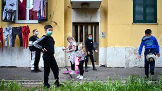 Des enfants jouent devant leur immeuble du quartier de San Basilio à Rome (Italie), le 18 avril 2020. (ALBERTO PIZZOLI / AFP)