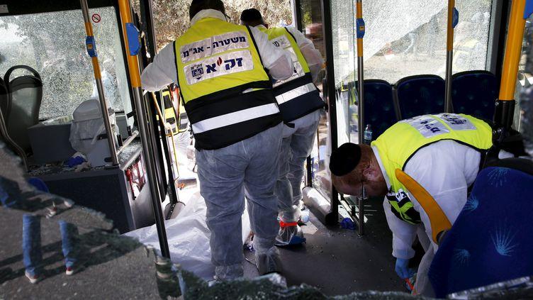 Des membres des secours israéliens interviennent dans le bus visé par une attaque le 13 octobre à Jérusalem. (RONEN ZVULUN / REUTERS)