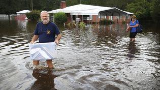 Des habitants évacuent leurs affaires de leur maison de Spring Lake, en Caroline du Nord, pour fuir la montée des eaux sur le passage de la dépression tropicale Florence, le 17 septembre 2018. (JOE RAEDLE / AFP)