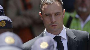 Oscar Pistorius est escorté par des policiers en sortant du tribunal de Pretoria (Afrique du Sud), le 17 octobre 2014. (THEMBA HADEBE / AP / SIPA)