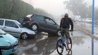 Un cycliste constate les dégâts causés par les orages, le 4 octobre 2015, àMandelieu-la-Napoule (Alpes-Maritimes). (BORIS HORVAT / AFP)
