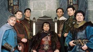"""Le Roi Arthur, incarné par Alexandre Astier (assis, au centre), entouré des """"chevaliers"""" de la Table Ronde. (M6 Groupe)"""