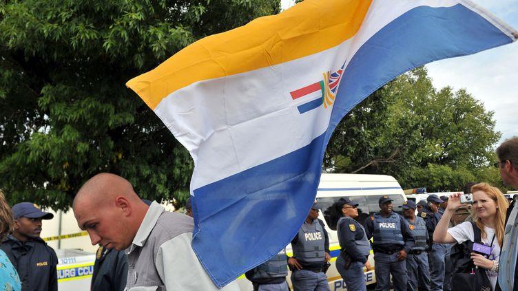 Des sud-Africains soutenant le Mouvement de résistance Afrikaners (AWB), un groupuscule suprémaciste blanc, brandissent le drapeau de l'apartheid devant le tribunal sud-africain de Ventersdorp, le 6 avril 2010. (ALEXANDER JOE / AFP)