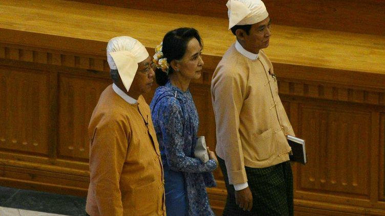 Le président Htin Kyaw (à gauche), premier dirigeant birman à n'avoir aucun lien avec l'armée depuis plus d'un demi-siècle, a prêté serment mercredi 30 mars 2016 devant le Parlement dominé par les élus de la Ligue nationale pour la démocratie (LND) de la lauréate du prix Nobel de la paix Aung San Suu Kyi (au centre). La «dame de Rangoun», dont le parti a remporté une victoire écrasante lors des législatives de novembre, a confié à ce proche la charge de diriger le pays, étant elle-même tenue à l'écart de la fonction suprême par la Constitution rédigée par l'ancienne junte militaire. (ROMEO GACAD / AFP)