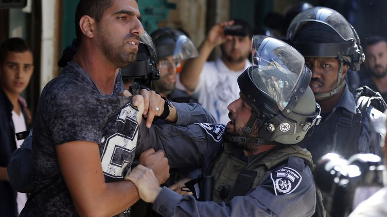 Des policiers israéliens tentent de maîtrisier un Palestien à Jérusalem-Est, le 28 septembre 2015. (AHMAD GHARABLI / AFP)