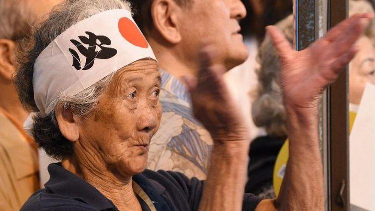 Une Japonaise portant un bandeau avec le drapeau national applaudit le Premier ministre japonais Shinzo Abe en meeting éléctoral à Tokyo, le 9 juillet 2016. (TORU YAMANAKA / AFP)