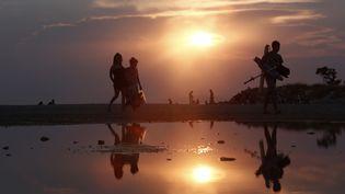 Des personnes quittent la plage de Glyfada (Grèce), le 25 août 2013. (JOHN KOLESIDIS / REUTERS)