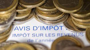 Un avis d'imposition sur le revenu et des pièces de 1 euro photo réalisée le 7 septembre 2012. (JOEL SAGET / AFP)