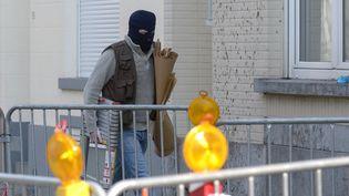 Un policier entre dans un immeuble de Bruxelles, le 16 mars 2016, au lendemain d'une opération anti-terroriste menée par les polices belge et française, dans le cadre de l'enquête sur les attentats de Paris en novembre 2015. (JOHN THYS / AFP)