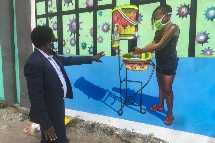 Henri Kalam Akulez, directeur de l'Académie des Beaux-Arts de Kinshasa devant une fresque visant à lutter contre la propagation du coronavirus, 18 juin 2020 (SAMIR TOUNSI / AFP)