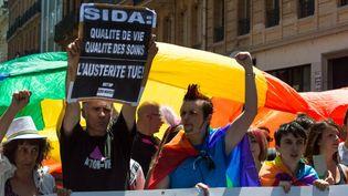 Un participant à la Gay Pride de Toulouse (Haute-Garonne) brandit une affiche pour alerter sur la dégradation des soins apportés aux malades dusida, le 20 juin 2015 (CLEMENT GRUIN / CITIZENSIDE.COM / AFP)
