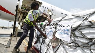 Des caisses de vaccins AstraZeneca contre le Covid-19 sont déchargées d'un avion sur le tarmac de l'aéroportFelix Houphouet Boigny, à Abidjan, en Côte d'Ivoire, le 26 février 2021. (SIA KAMBOU / AFP)