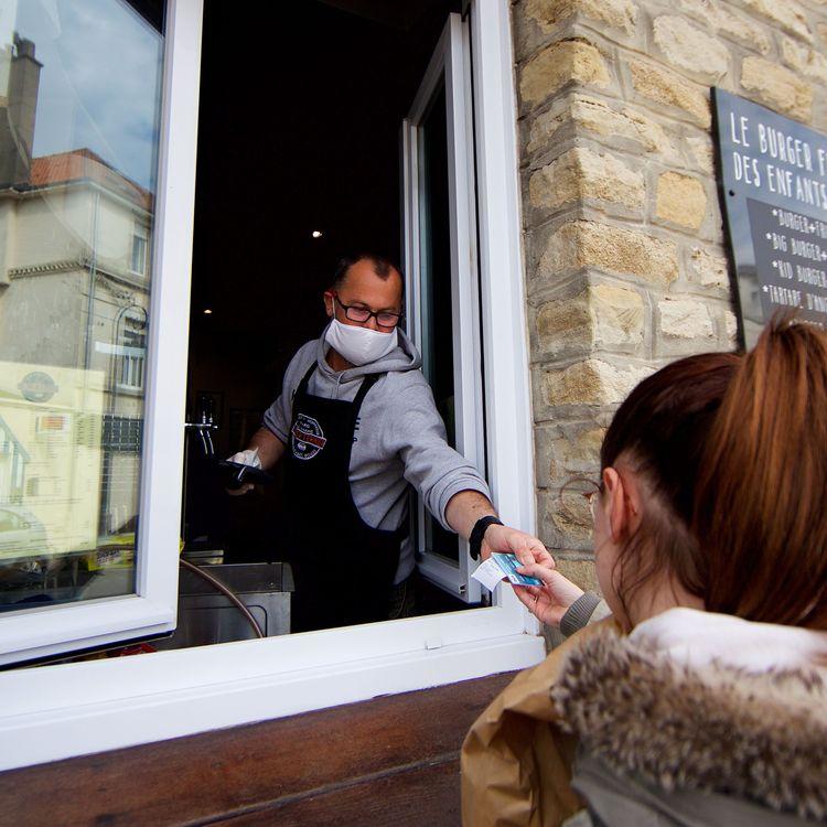Un restaurateur sert des burgers à emporter à une cliente, le 17 avril 2020, pendant le confinement, à Wimereux (Pas-de-Calais). (MAXPPP)