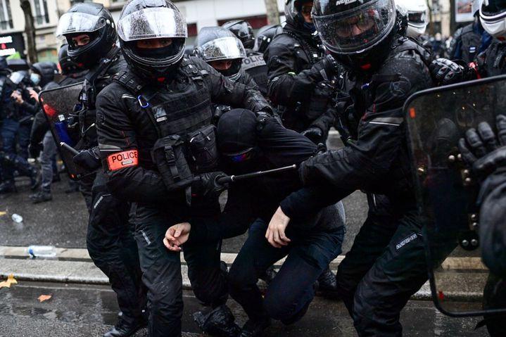 """Des policiers de la Brav procèdent à l'interpellation d'une personne le 12 décembre 2020 à Paris lors de la manifestation contre la proposition de loi sur la """"sécurité globale"""". (MARTIN BUREAU / AFP)"""
