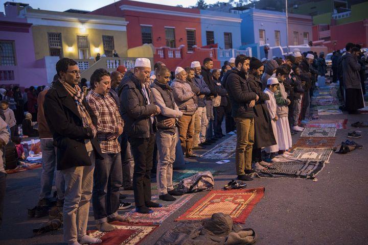 Des hommes prient après la célébration de l'iftar, à Wale Street, dans le quartier de Bo-Kaap, le 1er juin 2018 (RODGER BOSCH / AFP)