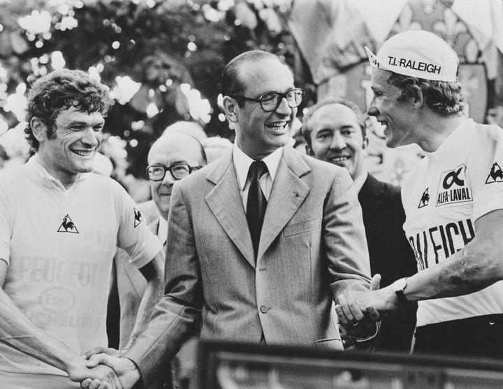 Le maire de Paris Jacques Chirac (au centre) remet le maillot jaune à Bernard Thévenet (à gauche) à l'arrivée du Tour de France 1977 sur les Champs-Elysées et salueDietrich Thurau (à droite), second de l'épreuve. (KEYSTONE / HULTON ARCHIVE)