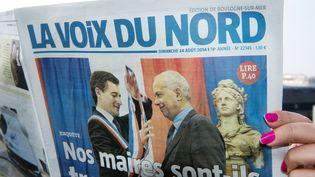 """Un lecteur tenant un exemplaire du quotidien régional """"La Voix du Nord"""", en septembre 2014 (photo d'illustration) (DENIS CHARLET / AFP)"""