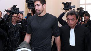 Nikola Karabatic en compagnie de son avocat Jean-Robert Nguyen Phungquittant le tribunal de Montpellier le 16 octobre 2012 (PASCAL GUYOT / AFP)