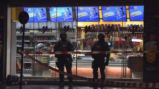 Deux policiers en poste devant l'entrée de la gare centrale de Munich (Allemagne), fermée en raison d'une menace terroriste, la nuit du 31 décembre au 1er janvier 2016. (CHRISTOF STACHE / AFP)