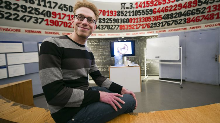 L'écrivain et savant britannique autiste, Daniel Tammet, pose le 14 mars 2013 au Palais de la découverte devant une banderole déroulant le nombre Pi. (LIONEL BONAVENTURE / AFP)