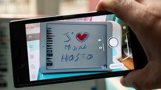 Illustration d'un message pour les professionnels medicaux (medecins, infirmiers, soignants). J'aime mon hosto, message ecrit sur une tablette, smartphone.  (RICCARDO MILANI / HANS LUCAS)