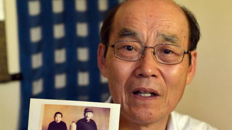 Yohachi Nakajima, 73 ans, tient une photo de ses parents adoptifs chinois (AFP/YOSHIKAZU TSUNO)