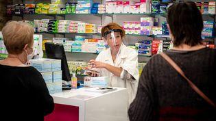 Une pharmacienne face à des clients, dans une officine de Dordogne, le 15 mai 2020. (GARO / PHANIE / AFP)