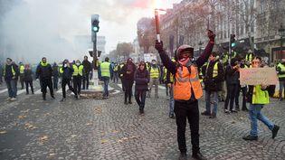 """Des manifestants se réclamant des """"gilets jaunes"""" sur les Champs-Elysées, le 24 novembre 2018 à Paris. (LUCAS BARIOULET / AFP)"""