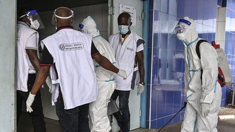 Deux agents de l'Institut National d'Hygiène Publique (INHP) portant des combinaisons de protection individuelle (EPI) contre le virus Ebola lors d'une opération de désinfection dans les locaux du Centre hospitalier universitaire (CHU) deCocody, à Abidjan, le 16 août 2021. (SIA KAMBOU / AFP)
