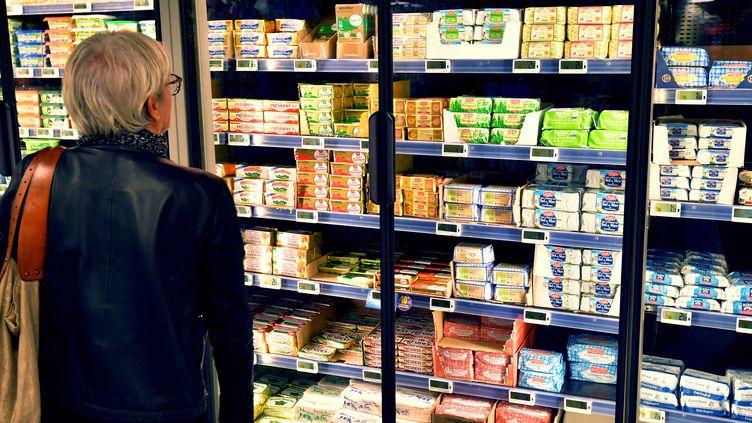 Une femme observe des plaquettes de beurre dans un supermarché à Nantes (Loire-Atlantique), le 20 octobre 2017. (LOIC VENANCE / AFP)