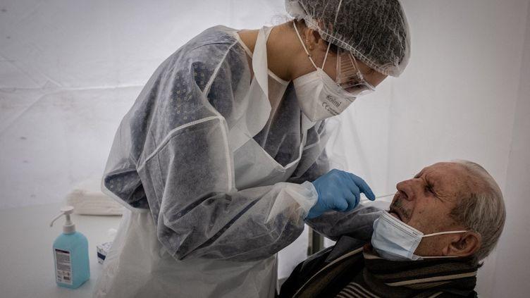 Un homme subit un test PCR, le 13 janvier 2021 à Saint-Etienne (Loire). (JEAN-PHILIPPE KSIAZEK / AFP)