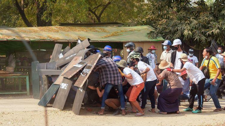 Des manifestants se réfugient derrière des boucliers pour se protéger face aux forces de l'ordre, le 7 mars 2021 à Bagan (Birmanie). (AFP)