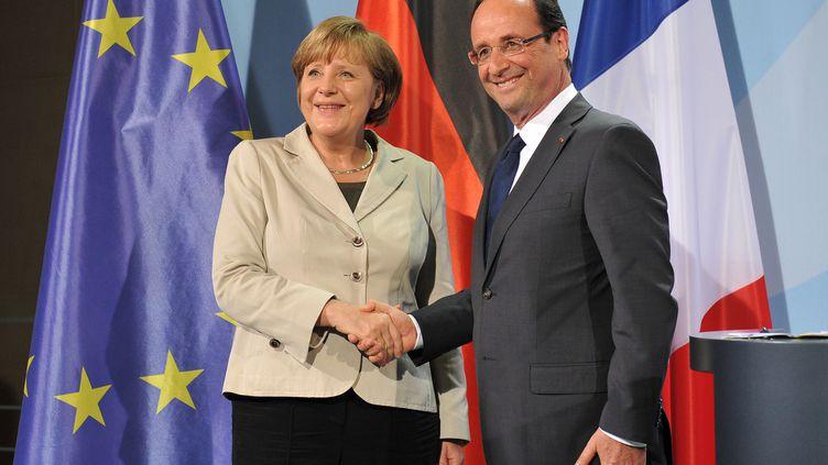 Poignée de main entre Angela Merkel et François Hollande à l'issue de leur première conférence de presse commune, à Berlin (Allemagne), le 15 mai 2012. (BERTRAND LANGLOIS / AFP)