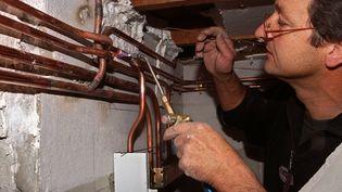Un homme s'essaie au metier de plombier. (DIDIER PALLAGES / AFP)