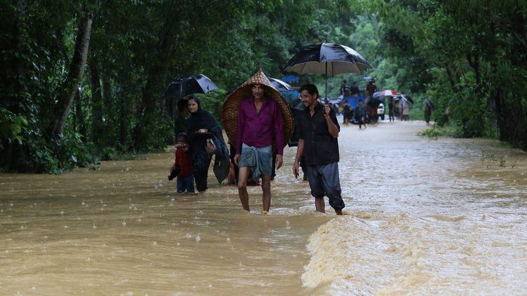 Des personnes marchent sur une route inondée, dimanche 14 juillet 2019 à Bandarban (Bangladesh). (REHMAN ASAD / NURPHOTO / AFP)