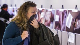 """Une femme émue par les photos de corps torturés et décharnés, extraites du rapport """"César"""", lors d'une exposition à New York, le 10 mars 2015 (LUCAS JACKSON / REUTERS)"""