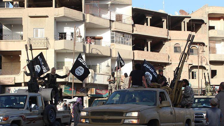 Des jihadistes du groupe Etat islamique paradent dans la ville de Raqqa, au nord de la Syrie, le 30 juin 2014. (WELAYAT RAQA / AFP)