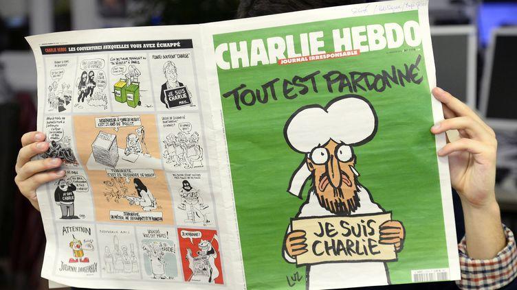 """Un homme lit le journal satirique """"Charlie Hebdo"""" daté du 14 janvier 2015, à Paris. (BERTRAND GUAY / AFP)"""