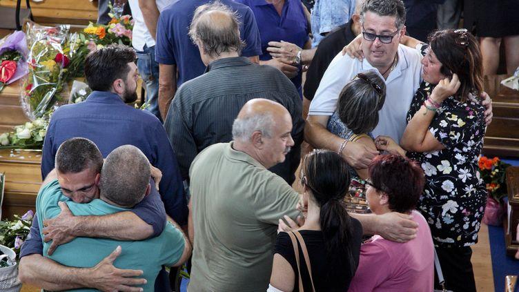 Des proches des victimes du séisme, qui a frappé l'Italie le 24 août 2016, lors des funérailles, trois jours plus tard, àPescara del Tronto (Italie). (ALESSIO PADUANO / ANADOLU AGENCY / AFP)