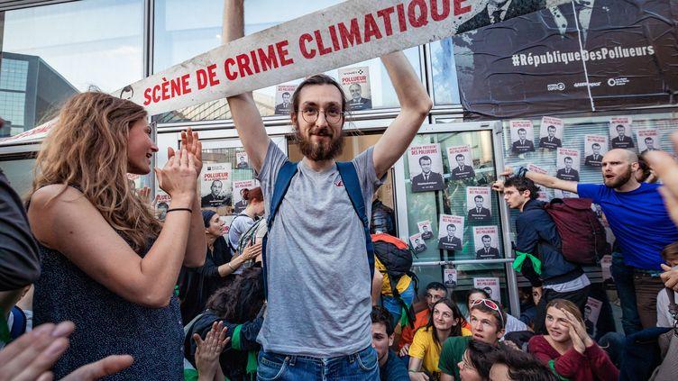 Un militant participe à une manifestation de plusieurs associations écologistes dont Greenpeace, sur le parvis du quartier d'affaires de la Défense (Hauts-de-Seine), le 19 avril 2019. (JULIEN HELAINE / HANS LUCAS / AFP)