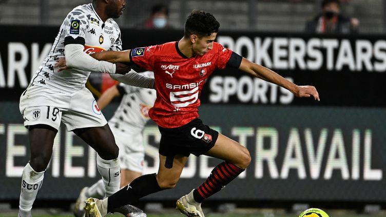 Le Rennais Nayef Aguerd (en rouge) tente de se défaire de l'Angevin Stéphane Bahoken. (DAMIEN MEYER / AFP)