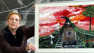 L'artiste rom autrichienne Ceija Stojka et l'une de ses oeuvres sur la déportation  (RAINER JENSEN / DPA)