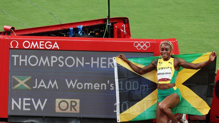 La JamaïcaineElaine Thompson-Herah pose avec son drapeau devant son temps en finale des JO de Tokyo, synonyme de nouveau record olympique, le 31 juillet 2021. (GIUSEPPE CACACE / AFP)