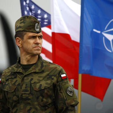 Un soldat polonais se tient devant des drapeaux américains, polonais et de l'Otan, à Swidwin (Pologne),lors de l'arrivée de 150 soldats américains pour des exercices militaires en Pologne et dans les pays baltes, le 23 avril 2014. (KACPER PEMPEL / REUTERS)