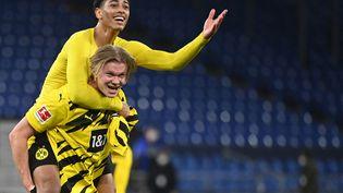Jude Bellingham sur le dos d'Erling Haaland après la victoire du BVB contre Schalke, le 20 février 2021. (INA FASSBENDER / AFP)