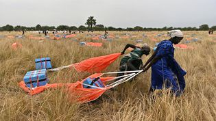 Des villageoises récupèrent de l'aide alimentaire larguée par avion au Soudan du Sud, le 6 février 2020. (TONY KARUMBA / AFP)
