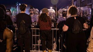 Des manifestants face à des policiers, lors d'une manifestation à Philadelphie (Etats-Unis) au lendemain de la mort de Walter Wallace Junior, abattu par deux policiers, le 26 octobre 2020. (GABRIELLA AUDI / AFP)