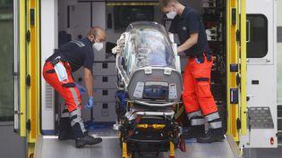Des ambulanciers allemands chargent dans une ambulance le brancard qui a servi à transférer l'opposant russe Alexeï Navalny à l'hôpital de la Charité à Berlin le 22 août 2020. (ODD ANDERSEN / AFP)