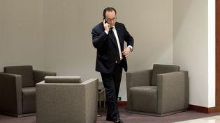 François Hollande au téléphone, le 20 mars 2015, à Bruxelles (Belgique). (ALAIN JOCARD / AFP)